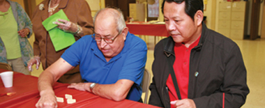 Two men play dominoes at senior center.