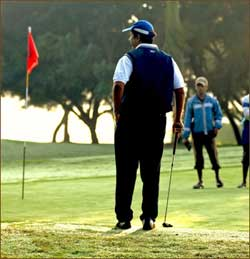 Golfer standing near hole